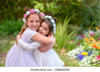 Two happy multiracial children playing outdoors. Kids having fun in spring park. Friends hugging on nature background. Side view portrait.