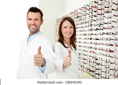 Two happy opticians, optometrists showing thumbs up in optical shop