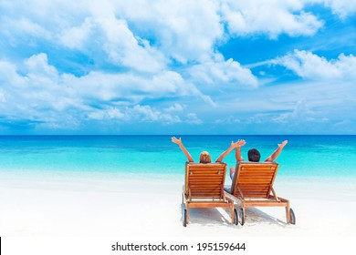 Two happy people having fun on the beach, sitting on comfortable sunbed with raised up hands for joy, rear view, summer holidays concept