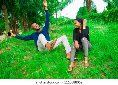 two happy people sitting on the grass outside laughing