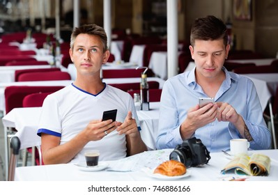 Two happy  positive men sitting with coffee and looking at mobiles in cafe