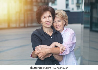 Two happy positive women, female friends standing outdoors office after work. Couple in love hugging, holding each other. Mature senior ladies. LGBT community, lesbian, homosexual, business concept
