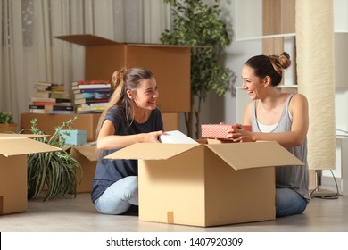 Two happy roommates talking unboxing gelongings moving home sitting on the floor