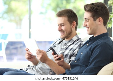 two happy roommates using a tablet and smart phone sitting on a sofa in the living room at home