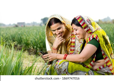 Two happy rural women using phone on agricultural field