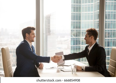 Two happy satisfied businessmen shaking hands over desk after successful negotiations, closing sealing deal, big window city building at background, smiling partners binding agreement with handshake