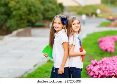Two happy school girls wearing school  uniform in the park