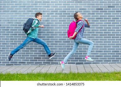 Two happy schoolchildren with backpacks run to school on street next to an Brick Wall. Cheerful cute children pupils Teen Girl and Boy Back to School. Concepts of friends, childhood and education.
