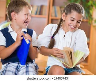 Two happy schoolchildren have fun in classroom at school