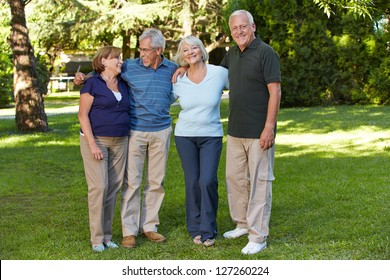 Two happy senior couples standing in the park of a retirement home