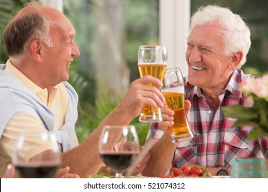 Two happy senior friends drinking a beer during dinner