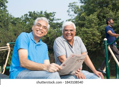 Two happy senior men reading newspaper at park outdoor