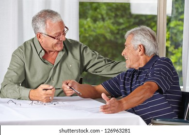 Two happy senior men solving crossword puzzle in a rest home