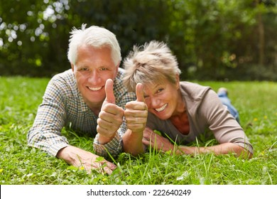 Two happy senior people laying in a meadow holding their thumbs up