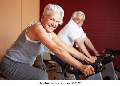 Two happy senior people on bikes in gym