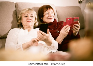 Two happy senior women together relaxing with phones on sofa at home
