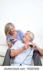 Two happy seniors playing computer games with game controller