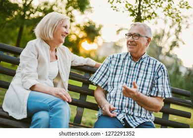 Two happy seniors are sitting and talking in park.
