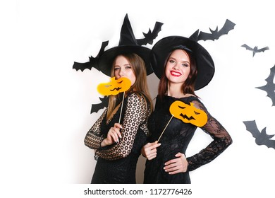 Two happy sexy women in black witch halloween costumes with pumpkin on party over white background
