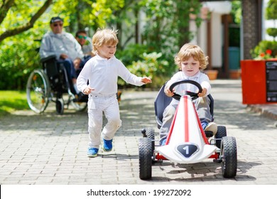 Two happy sibling boys playing with toy car in summer garden, outdoors.
