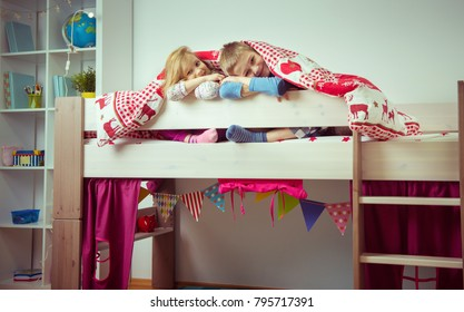 Two happy sibling children having fun in bunk bed under blanket