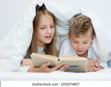 Two happy sibling children lying under blanket with book