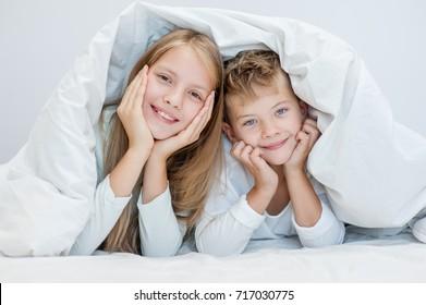 Two happy sibling children lying under blanket