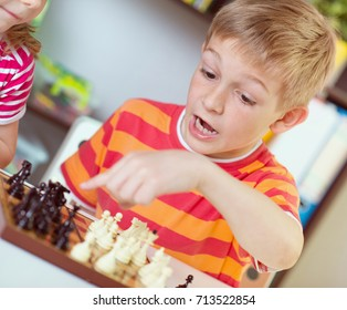 Two happy siblings playing chess at home