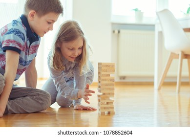 Two happy siblings playing a game with wooden blocks at home joyfully