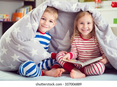 Two happy siblings reading book under the cover