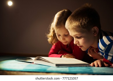 Two happy siblings reading book at darkness with flashlight at hiding place under the bed
