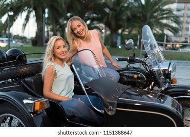Two happy sister blonde women on sidecar bike smiling and happy