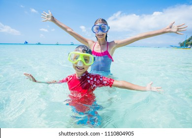 Two happy sister and brother in diving masks having fun together on the beach