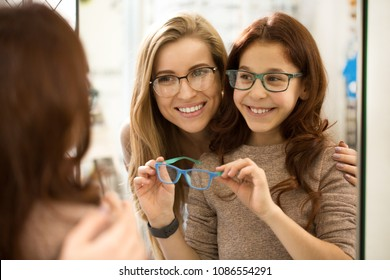 Two happy sisters wearing glasses smiling joyfully posing in front of the mirror at the opticians store. Beautiful woman and her little sister shopping for eyewear together