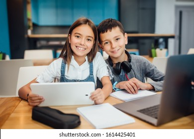 Two happy small friends writing homework , using smart digital tablet at modern blue classroom.