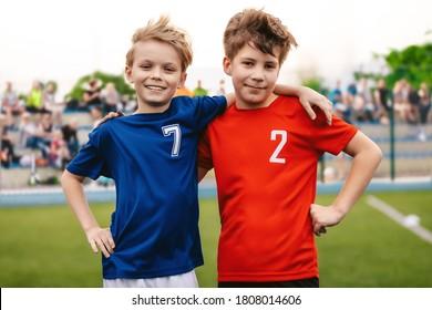 Zwei glückliche Lächelnde Jungen im Sportteam, die auf Gras Pitch stehen. Kinder, die sportliche Aktivitäten im Freien machen. Kinder in Sports Jersey Uniformen. Zuschauer und Eltern auf unscharfem Hintergrund