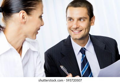 Two happy smiling businesspeople or client and businessman, giving pen for signing document. Teamwork, partnership, meeting, brainstorming, conculting and business success concept.