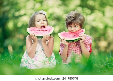 Two happy smiling child eating watermelon in  spring park, sitting on green grass. Picnic concept