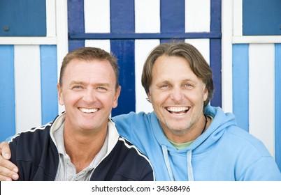 Two happy smiling gay men cuddling.