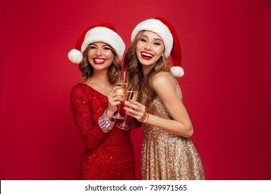 Two happy smiling girls in christmas hats toasting with champagne glasses and looking at camera isolated over red background