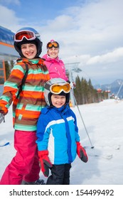 Two happy smiling kids in ski goggles and a helmet with his mother in the mountains