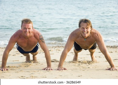 Two happy smiling mature men are performing push ups on a sandy beach.