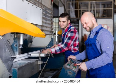 Two happy smiling workmen in uniform working on a machine in PVC shop and smiling