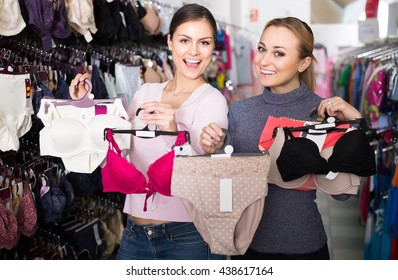 37f7ad2c2 two happy spanish female customers holding bras and panties in hands in underwear  store