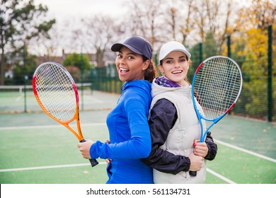 Two happy sporty girls tennis players with rackets standing back to back