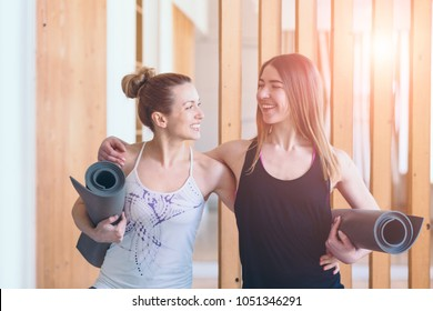 Two happy sporty women friends hugging, holding yoga mat and ready to start workout together yoga or pilates exercise indoor. Sun glare effect.