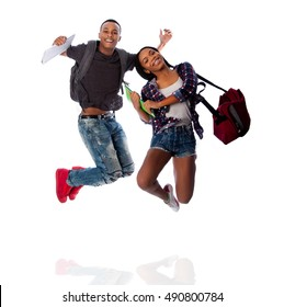 Two happy students jumping of happiness celebrating, carrying notepads and bags, on white.