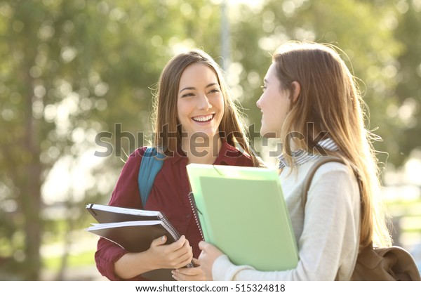 Two happy students walking and talking each other in a campus at sunset with a warm light