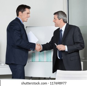 Two happy successful business partner shaking hands in the office