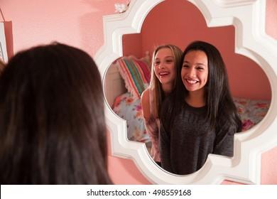 Two happy teen girls looking in mirror
